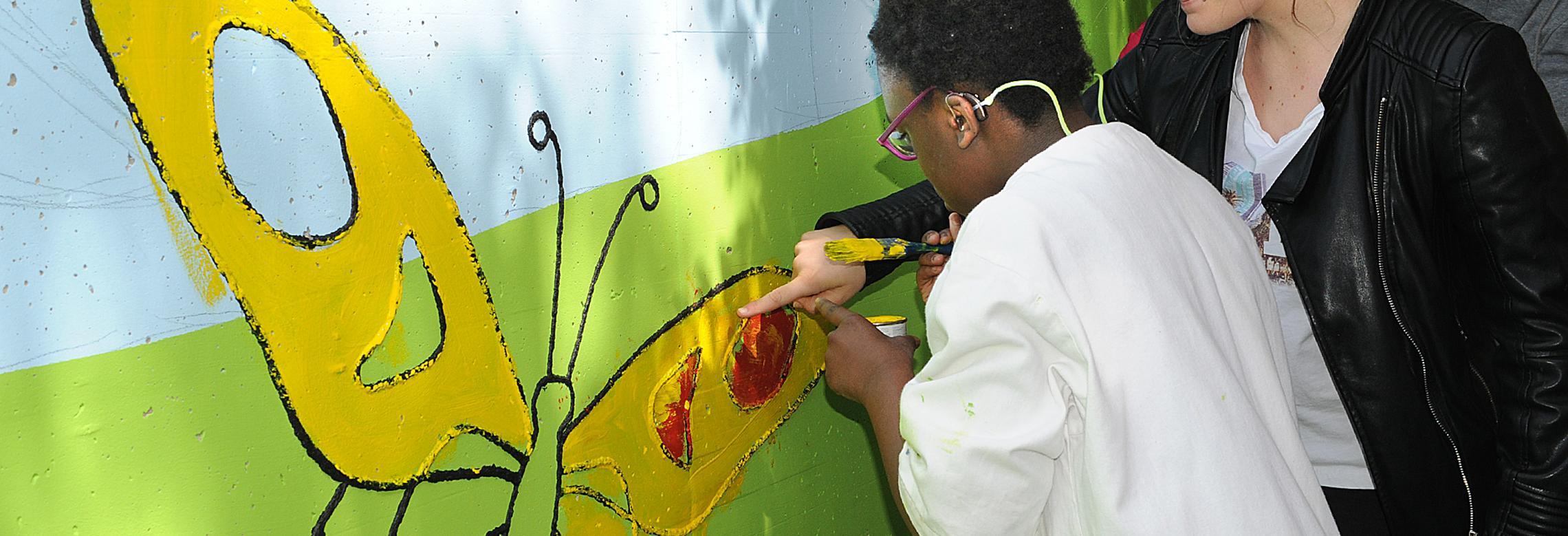 Une élève du CPHV dessine sur la fresque du bâtiment