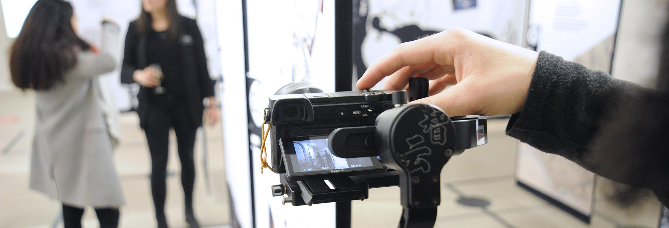 Image d'un vidéaste tournant une vidéo à deux personnes