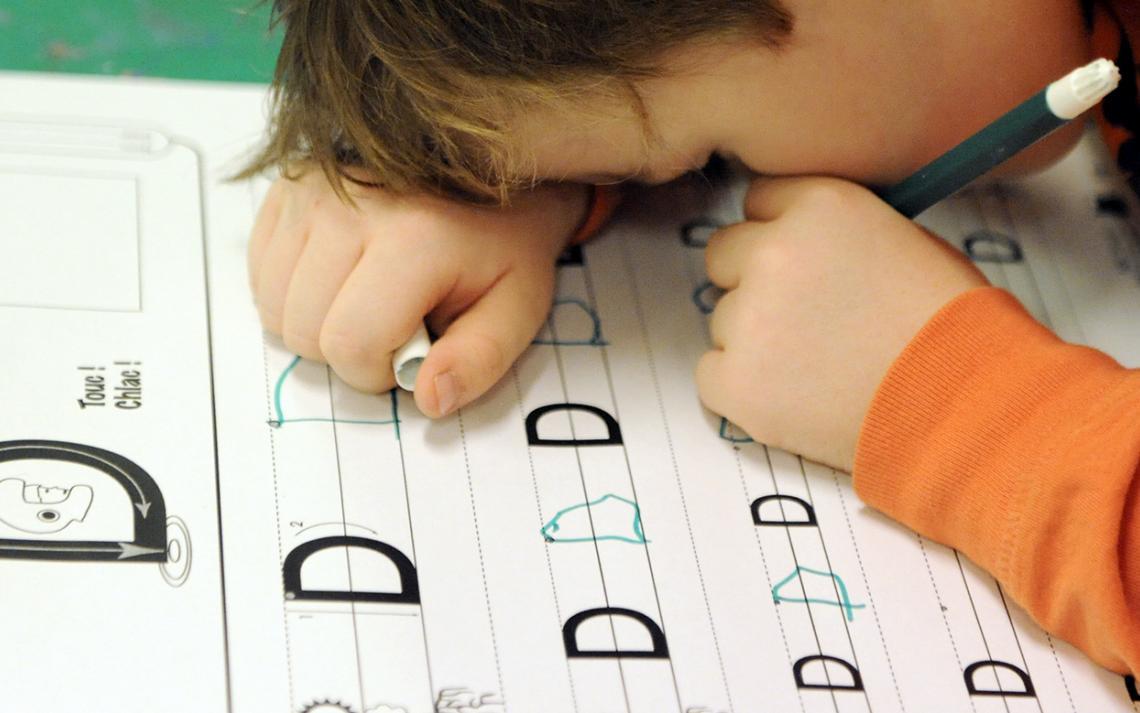 Image d'un enfant écrivant de très près