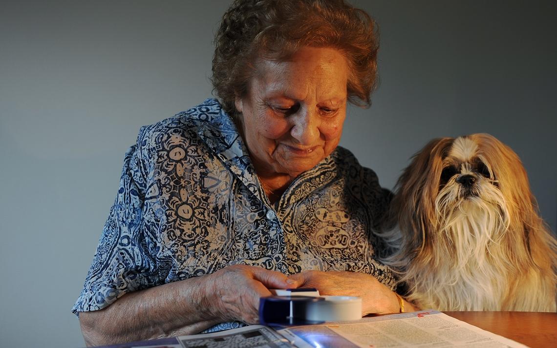 Image d'une dame lisant un journal avec une loupe