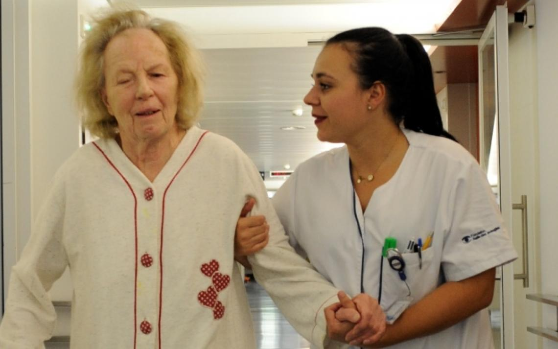 Une infirmière conduit une patiente dans sa chambre